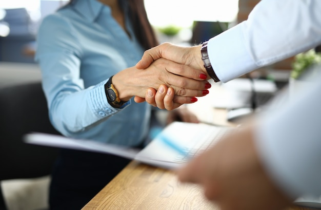 Businesswoman and businessman shaking hands in office.