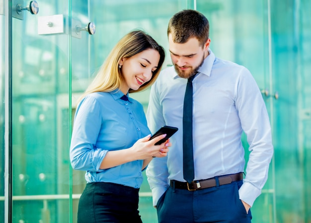Businesswoman and businessman with mobilephon planing a work