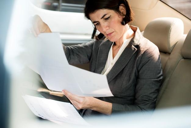 Businesswoman busy working car inside
