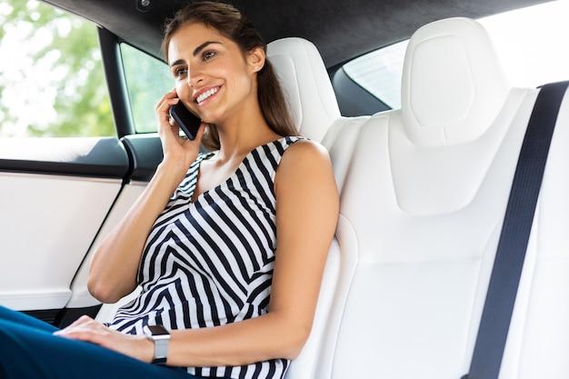 Вызов бизнес-леди. красивая сияющая бизнесвумен звонит мужу, сидя в машине