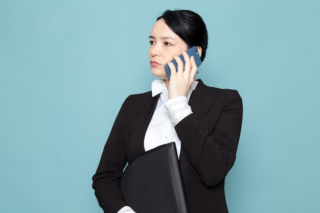 Businesswoman calling and holding folder