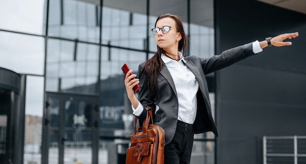 Businesswoman catches a taxi. a woman is waiting for a car and will go to a business meeting. business concept. girl with glasses in the city near work.