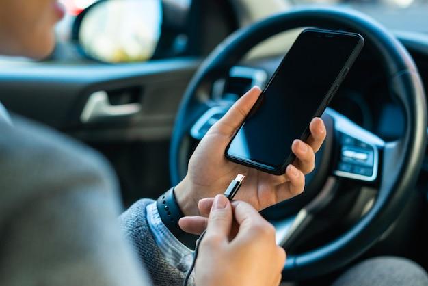 Деловая женщина заряжает свой телефон в машине