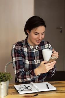 A businesswoman checking email via mobile phone and holding a coffee cup at home