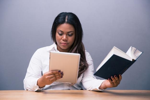 Деловая женщина выбирает между электронной книгой или бумажной книгой