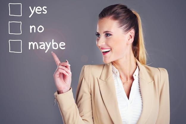 灰色の背景の上に「はい」と「いいえ」のどちらかを選択する実業家