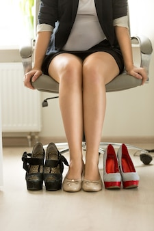 Businesswoman choosing between comfortable and sexy shoes
