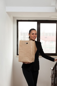 Businesswoman climbing stairs in startup company office hoding takeaway food meal bag during takeout