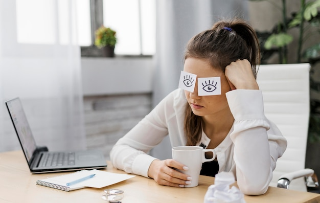 Businesswoman covering her eyes with drawn eyes on paper