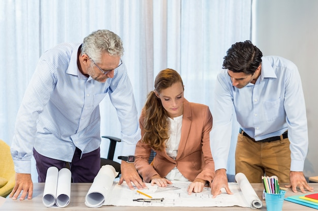 Businesswoman and coworkers discussing blueprint