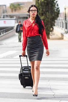Businesswoman crossing a crosswalk with a suitcase