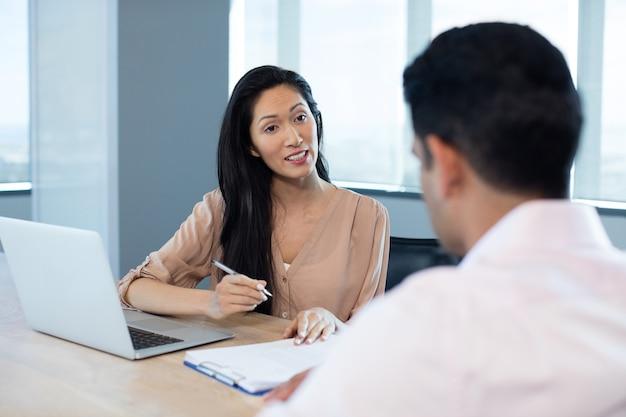 会議中に男性の同僚との契約を議論する実業家