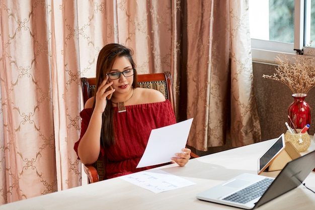 Businesswoman discussing document on phone