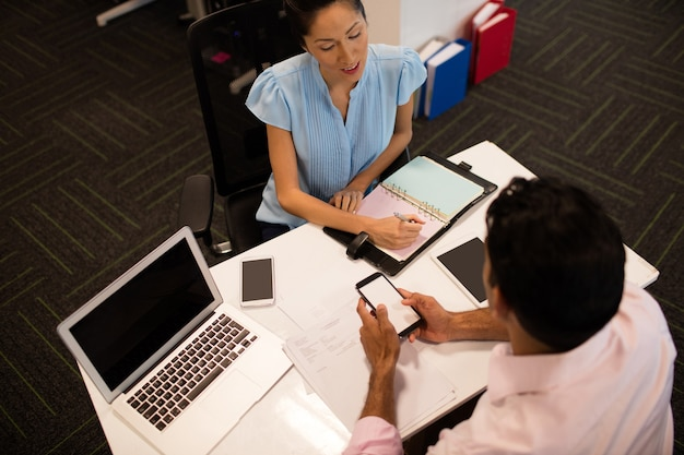 Businesswoman discussing with male colleague at desk