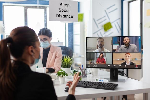 신생 기업 사무실의 마케팅 프레젠테이션에서 일하는 컴퓨터에 대한 온라인 화상 통화 회의 중에 원격 관리 팀과 논의하는 사업가입니다. 화면에 화상회의