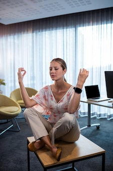Businesswoman doing yoga with hands in the air