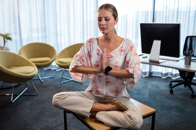 Businesswoman doing yoga with hands tied