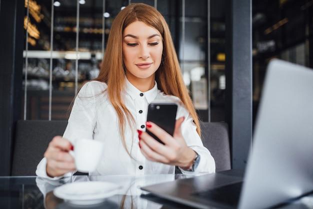 La donna di affari vestita in camicetta bianca e con capelli lisci lunghi si siede al tavolo con una tazza di caffè e guarda nel telefono con sguardo compiaciuto