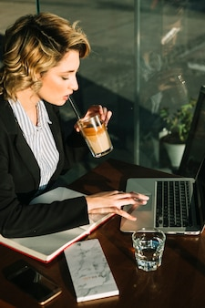 Businesswoman drinking chocolate milkshake while using laptop in restaurant