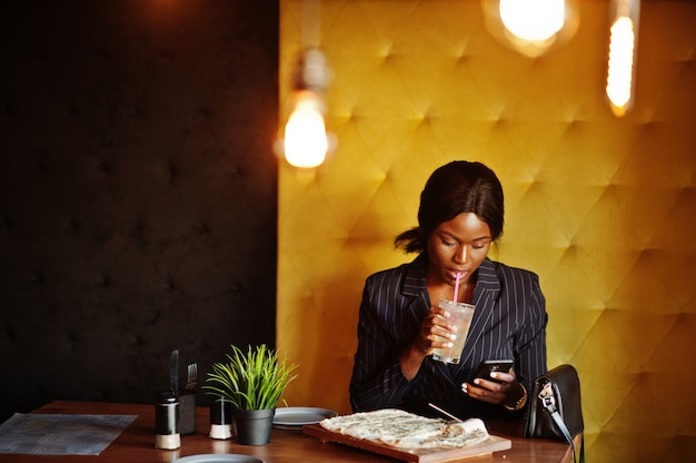 Businesswoman drinking cocktail lemonade in cafe