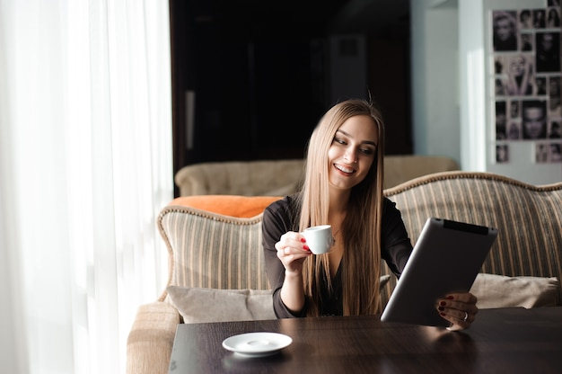 Businesswoman drinking coffee, tea in a coffee shop using a tablet.