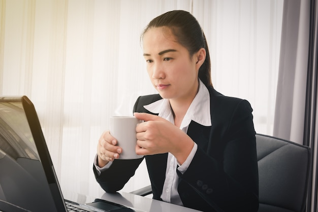 Businesswoman drinking coffee / tea and using labtop computer in office. time to relax concepts