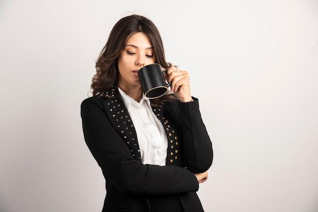 Donna d'affari che beve una tazza di tè su bianco