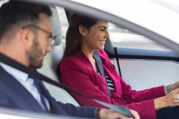 운전 하는 사업가. 남편이 근처에 앉아 차를 운전하는 동안 웃고 있는 아름다운 세련된 여성