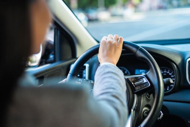 Деловая женщина за рулем своего автомобиля в городе
