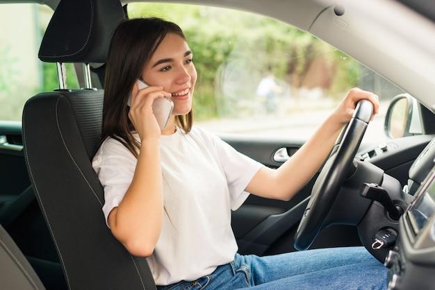 Деловая женщина за рулем машины и сердито разговаривает по телефону