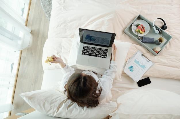 彼女のラップトップの画面上の販売レポートを分析するときに朝食に新鮮な果物を食べて、ベッドのコンセプトで働いている実業家
