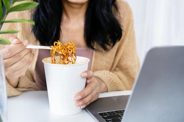 机の上にノートを持ってオフィスに座って職場でスパイシーな麺を食べる実業家