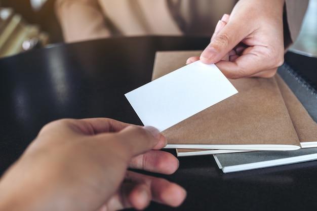 Деловая женщина обменивается визитной карточкой с ноутбуками на столе в офисе