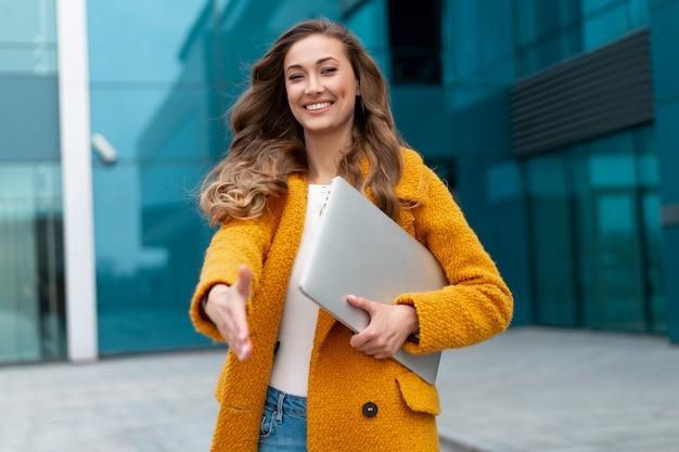 Деловая женщина протягивает руку готовое рукопожатие приветствие клиента деловой партнер подписывает сделку женщина hr встреча собеседование с сотрудником приятно познакомиться деловой человек с ноутбуком в желтом пальто, стоящий на открытом воздухе