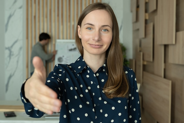 Businesswoman extending hand at camera offering handshake greeting guests looking at camera