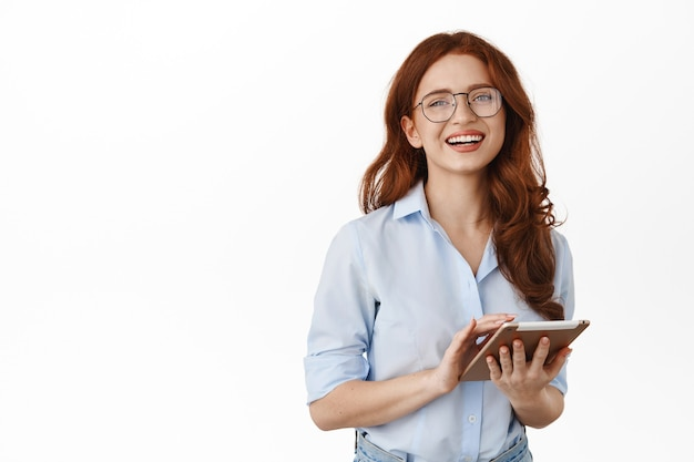 Businesswoman in eyeglasses and holding tablet posing on white