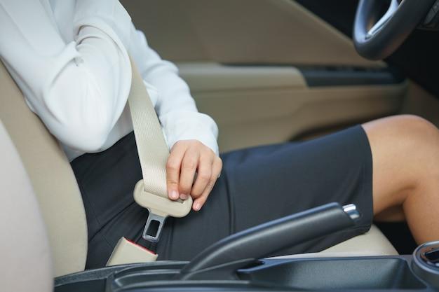 Предприниматель, скрепляющий ремень безопасности в автомобиле перед вождением