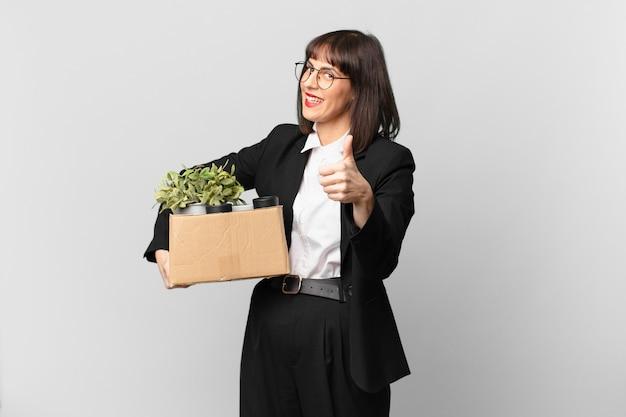 Деловая женщина чувствует себя гордой, беззаботной, уверенной и счастливой, позитивно улыбается и показывает палец вверх