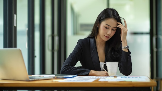 Businesswoman feeling stressed out from work, manager looking at financial report on table at office
