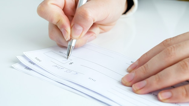 Businesswoman filling and signing banking cheque on office desk.
