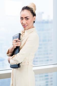 Businesswoman in front of skyscraper window