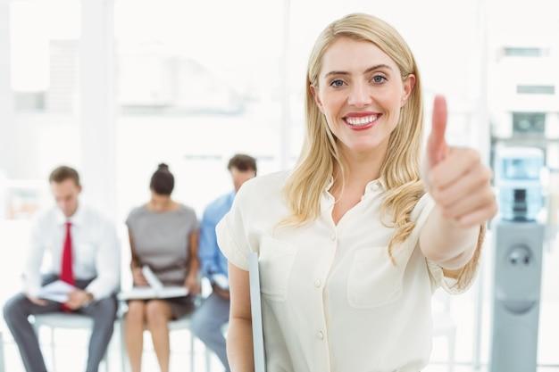 インタビューのために待っている人々に対して、ビジネスマンの身振りの親指