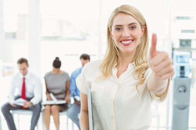 Businesswoman gesturing thumbs up against people waiting for interview