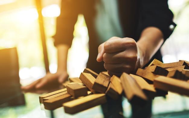 実業家は怒ってテーブルでタンブルタワーゲームの木製のブロックを破壊