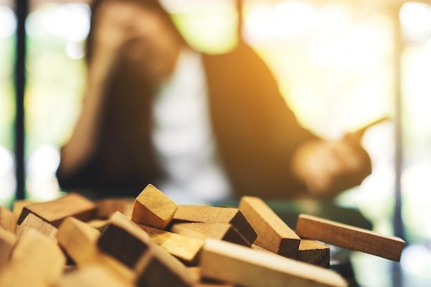 テーブルの上のタンブルタワーゲームの木製ブロックでオフィスでの仕事で問題を抱えている間に実業家がストレス