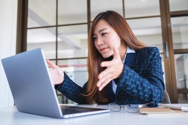 ビジネスウーマンは、オフィスでラップトップコンピューターで作業中にストレスを感じる