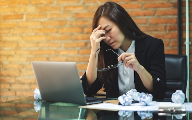 Businesswoman get stressed with screwed up papers and laptop on table while having a problem at work in office
