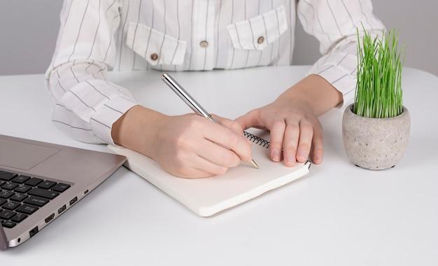 ノートパソコンのビジネスコンセプトに近い、デスクトップのホームオフィスに関する情報を書き留めるノートブックで作業する実業家の女の子の手。