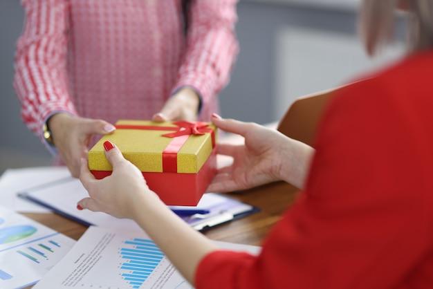 Деловая женщина дает подарок коллеге на рабочем месте подарки в концепции рабочего места