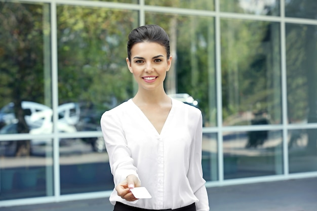 Businesswoman giving business card on window